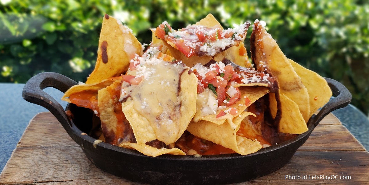SKILLET NACHOS - fresh tortilla chips, pepper jack cheese sauce, black beans, brisas sauce, pico de gallo, cotija cheese. Optional Add-ons: chicken tinga OR short rib